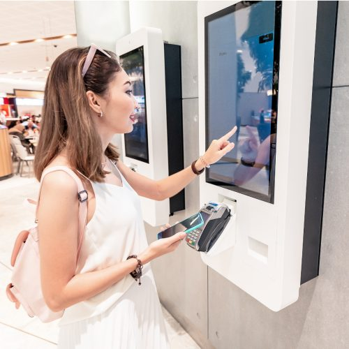 The girl makes an order in a fast food restaurant at the self-service terminal in the Mall. Modern technologies and displacement of manual labor